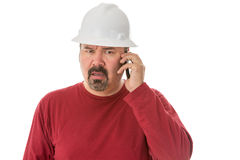 Workman looking confused talking on a mobile. Workman with a goatee beard wearing a hardhat listening to a call on his mobile phone with a look of shocked Stock Images