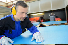 Workman looking at mark on blue sheet material Royalty Free Stock Image