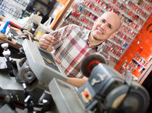 Workman making duplicates of keys Royalty Free Stock Image
