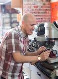 Workman making duplicates of keys Stock Photo