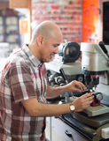 Workman making duplicates of keys Royalty Free Stock Photography