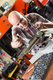 Workman making mailbox plate in workshop Stock Image