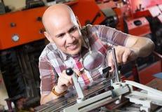 Workman making mailbox plate in workshop Stock Photos