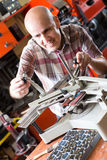 Workman making mailbox plate in workshop Royalty Free Stock Image