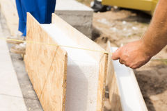 Workman measuring a prefab wall panel. Workman measuring a prefab wooden wall panel with insulation on a construction site prior to installing it Stock Photography