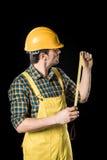 Workman with meter roller. Workman in yellow hard hat holding meter roller on black Stock Image