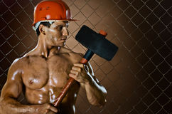 Workman. Muscular worker , in  safety helmet  with big tup  in hands, on netting fence background Stock Photography