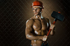 Workman. Muscular worker , in  safety helmet  with big tup  in hands, on netting fence background Stock Images