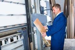 Workman operating automatic machinery Stock Photo