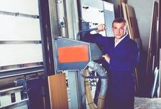 Workman operating automatic machinery. Cheerful workman 40s operating large automatic saw machinery Stock Photos