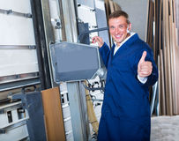 Workman operating automatic machinery. Cheerful workman in uniform operating large automatic saw machinery Stock Photos