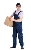 Workman in overalls hands a cardboard box. Workman in overalls and blue peaked cap hands a cardboard box, isolated on white. Transportation service Stock Photos