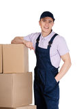 Workman in overalls stands near parcels Stock Photo
