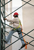 Workman painting a building facade from a scaffold Royalty Free Stock Image