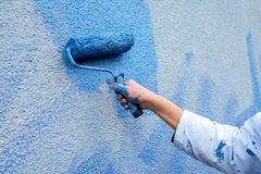 Workman painting the wall in blue Stock Photos