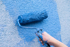 Workman painting the wall in blue Royalty Free Stock Image