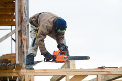 Workman. With petrol-powered saw, cut up  wooden  brick on building site framehouse Stock Images