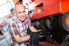 Workman polishing boots in workshop. Friendly mature workman giving leather boots a high polish in workshop Royalty Free Stock Photos