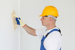 Workman polishing wall. Portrait of workman polishing wall Royalty Free Stock Photo