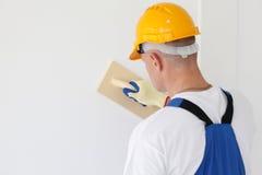 Workman polishing wall. Portrait of workman polishing wall Royalty Free Stock Photography