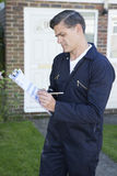 Workman Preparing Estimate For Work On House Exterior. Workman Preparing Estimate For Work On House stock photo