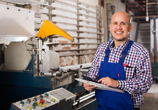 Workman at professional lathe. Middle age workman at professional lathe in plant Royalty Free Stock Images