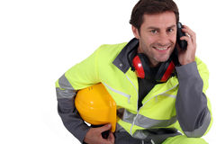Workman in protective gear. With mobile phone Royalty Free Stock Photo