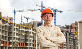 Workman in red helmet on background of buildings Stock Photography