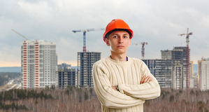 Workman in red helmet on background of buildings Stock Photos