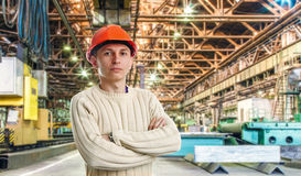 Workman. In red helmet in the workshop of machinery plant Royalty Free Stock Images