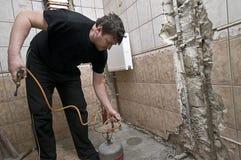 Workman renovating bathroom. Closeup of single middle aged workman using tool in bathroom or washroom renovation Royalty Free Stock Photo