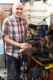 Workman repairing pair of shoes. Joyful mature workman repairing pair of shoes and replacing heeltaps Royalty Free Stock Photo