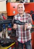Workman repairing pair of shoes. Joyful mature workman repairing pair of shoes at workshop Stock Image