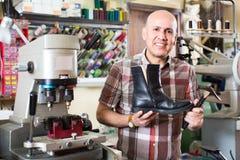 Workman repairing pair of shoes Stock Photo