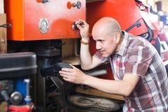Workman repairing pair of shoes Royalty Free Stock Images