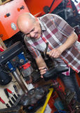 Workman repairing pair of shoes. Mature shoe repairman replacing heeltaps on shoe at workshop and smiling Stock Photo