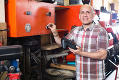 Workman repairing pair of shoes. Positive mature shoe repairman repairing pair of shoes at workshop Royalty Free Stock Image