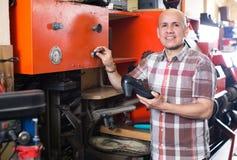 Workman repairing pair of shoes Royalty Free Stock Image