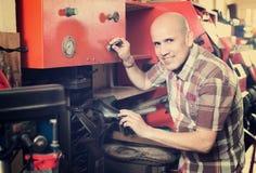 Workman repairing pair of shoes. Professional mature workman replacing heeltaps on shoe at workshop Stock Photo