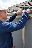Workman Replacing Guttering On Exterior Of House Royalty Free Stock Image
