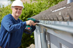 Workman Replacing Guttering On Exterior Of House. Portrait Of Workman Replacing Guttering On Exterior Of House Stock Photography