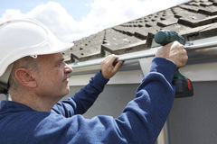 Workman Replacing Guttering On Exterior Of House. Workman Replaces Guttering On Exterior Of House Stock Photo