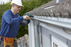 Workman Replacing Guttering On Exterior Of House. Workman Replaces Guttering On Exterior Of House Stock Photos