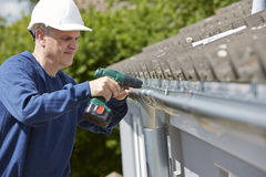 Workman Replacing Guttering On Exterior Of House. Using Drill Stock Images