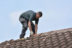 Workman replacing roof tiles and ridge tiles Stock Images