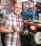 Workman resharpening knives on machine Stock Image