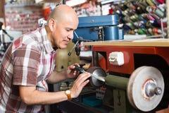 Workman resharpening knives on machine Stock Photo