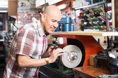 Workman resharpening knives on machine. Senior workman resharpening knives on interlock spiral wheel system machine at workshop Stock Image