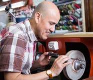 Workman resharpering knives on interlock spiral wheel system mac Stock Image