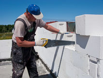 Workman sawing blocks. Side view of middle aged workman sawing aerated concrete block on wall Royalty Free Stock Photo